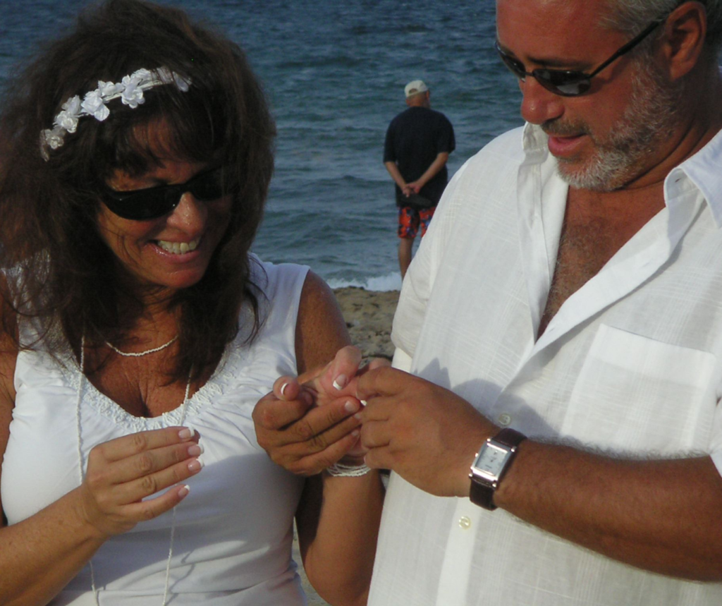 Couple exchanges rings on the beach